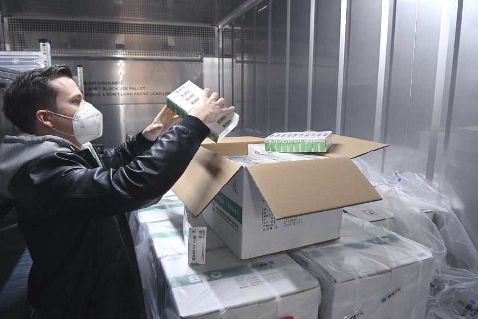 An employee checks the newly arrived coronavirus vaccines from Chinese pharmaceutical company Sinopharm at the logistics base set up to in the parking lot of the government office in the 13th district of Budapest, Hungary, Monday, March 29, 2021. (Noemi Bruzak/MTI via AP)