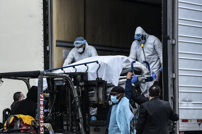 """<span class=""""caption"""">Because of COVID-19, hospitals had to use refrigerated trucks as temporary morgues. Here, medical workers remove a body from one of those trucks outside Brooklyn Hospital in New York City.</span> <span class=""""attribution""""><a class=""""link rapid-noclick-resp"""" href=""""https://www.gettyimages.com/detail/news-photo/medical-workers-remove-a-body-from-a-refrigerated-truck-news-photo/1208727616?adppopup=true"""" rel=""""nofollow noopener"""" target=""""_blank"""" data-ylk=""""slk:Getty Images / Stephanie Keith"""">Getty Images / Stephanie Keith</a></span>"""