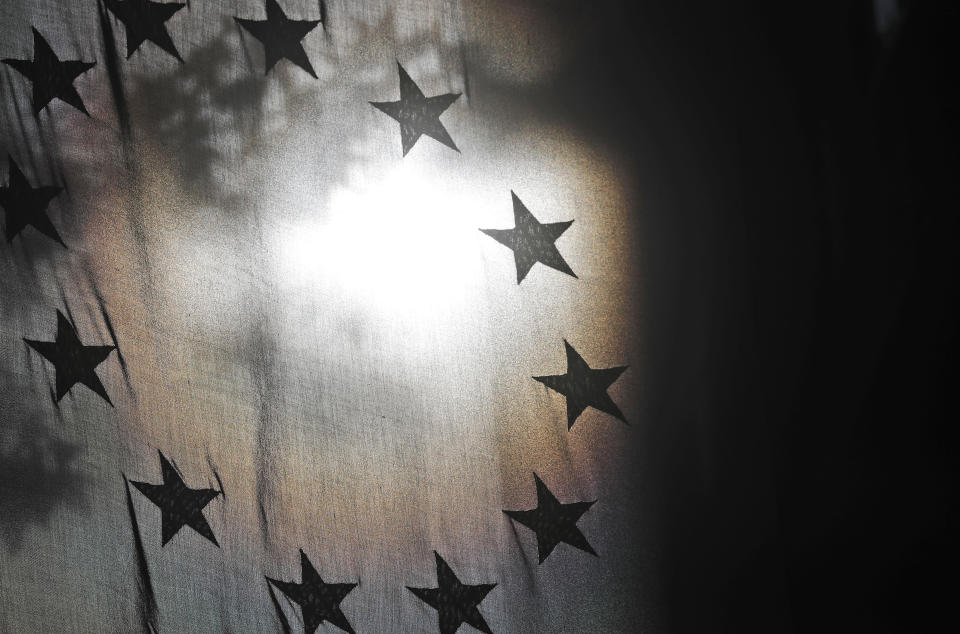 The stars of the EU flag are seen against the sun at the Europa House in London, Monday, Oct. 19, 2020. According to media reports, European Commission vice president Maros Sefcovic has met Chancellor of the Duchy of Lancaster Michael Gove for talks on the EU-UK trade deal. (AP Photo/Frank Augstein)