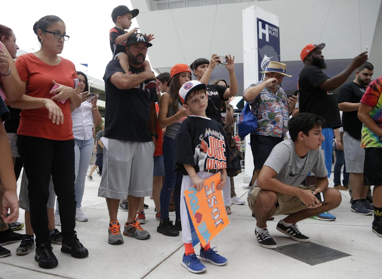 Fans photograph a makeshift memorial for Miami Marlins pitcher Jose Fernandez before a baseball game between the Miami Marlins and the New York Mets, Monday, Sept. 26, 2016, in Miami. Fernandez died in a boating accident early Sunday. (AP Photo/Lynne Sladky)