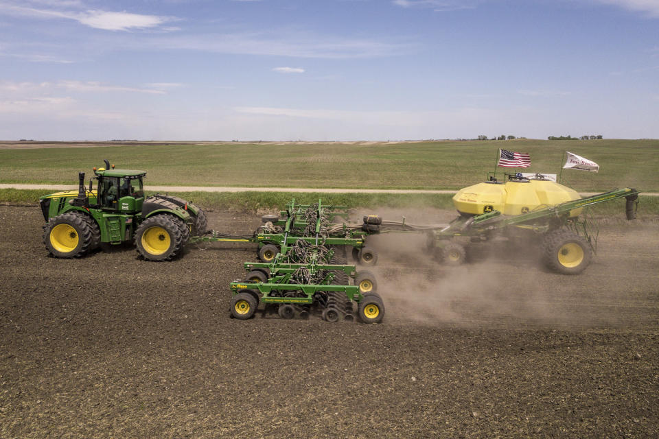 In this photo provided by Farm Rescue, volunteers plant crops on Paul Ivesdal's farm June 3, 2020 in Edmore, N.D. The wet spring offered only a tiny window for planting, so when Ivesdal fell ill to a coronavirus infection he knew the timing couldn't be worse. Thanks to Farm Rescue, Ivesdal got his crop in even as he was rushed to a hospital and spend eight days on a ventilator. The nonprofit organization's help meant that although Ivesdal spent a summer in rehabilitation to recover his walking ability and even now tires more easily, he'll be able to keep farming. (Dan Erdmann/Farm Rescue via AP)