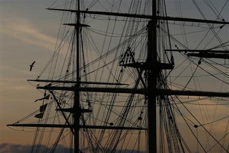 A seagull flies past the HMS Warrior during sunset at the Historic Dock Yard in Portsmouth November 26, 2013. The British shipbuilding industry has been through a turbulent time after defence contractor BAE Systems announced in November that it planned to lay off 1,775 ship workers across the UK. The cuts signal the end of more than 500 years of shipbuilding in Portsmouth on England's south coast. REUTERS/Stefan Wermuth