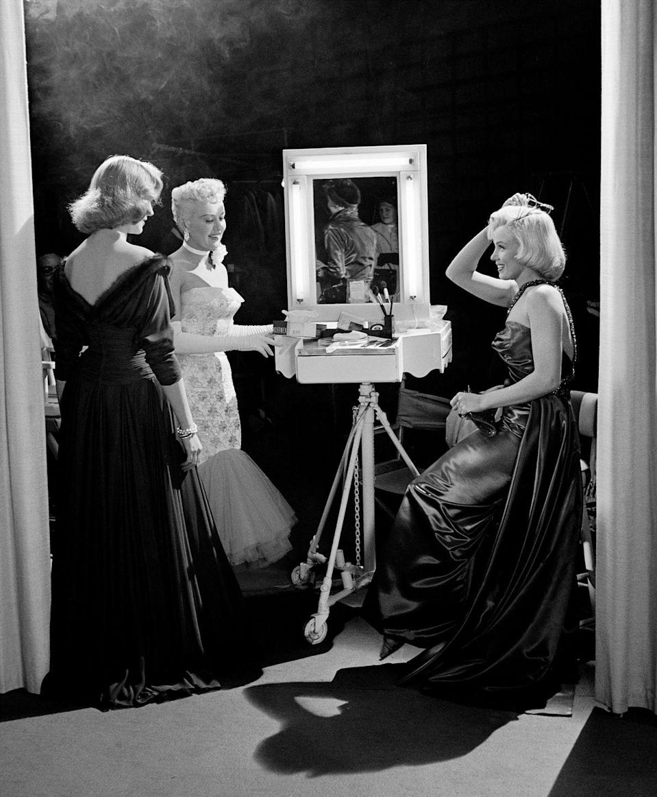 <p>Actresses Betty Grable, Lauren Bacall, and Marilyn Monroe touch up their hair and makeup while filming How to Marry a Millionaire. </p>