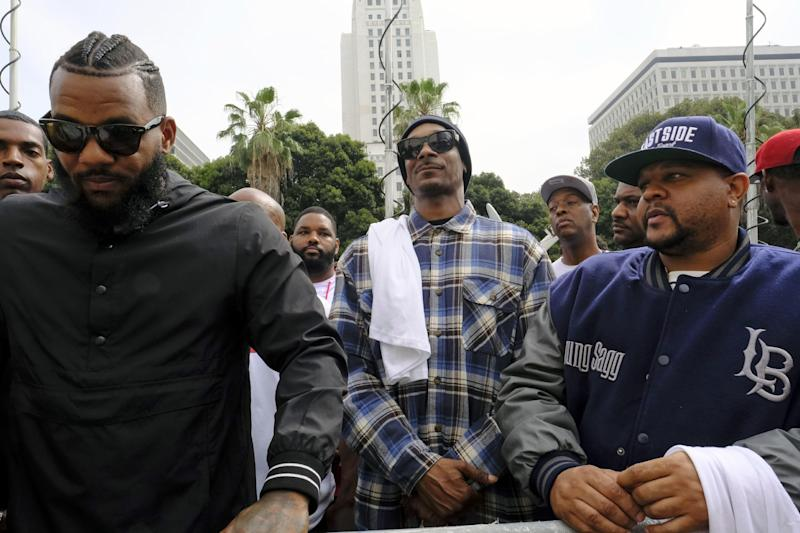 Rappers The Game, left, and Snoop Dogg, center, appear at a peaceful unification march outside of the graduation ceremony for the latest class of Los Angeles Police recruits in Los Angeles, Friday, July 8, 2016. Snoop shook hands with police officials and told reporters he hoped his presence would help reintroduce the black community to the Police Department and open a dialogue. The gathering comes a day after the shooting deaths of multiple police officers in Dallas on Thursday night. (AP Photo/Richard Vogel)