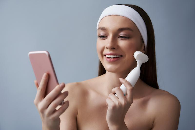 Close up portrait of attractive brunette girl in white headband holding pink smartphone while massaging cheek with electric brush cleanser. She looking at phone display and smiling