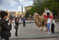 Tourists pose for photos as one of them sits atop a camel outside the Id Kah Mosque in Kashgar northwestern China's Xinjiang Uyghur Autonomous Region, during a government organized visit on April 19, 2021. Four years after Beijing's brutal crackdown on largely Muslim minorities native to Xinjiang, Chinese authorities are dialing back the region's high-tech police state and stepping up tourism. But even as a sense of normality returns, fear remains, hidden but pervasive. (AP Photo/Mark Schiefelbein)