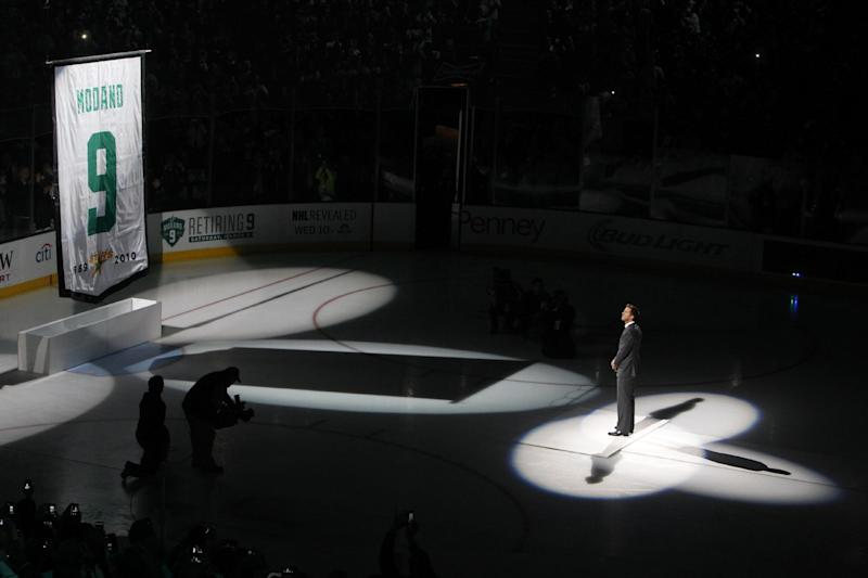 Former Dallas Stars player Mike Modano watches as a banner bearing his jersey number is raised before the Stars' NHL hockey game against the Minnesota Wild, Saturday, March 8, 2014, in Dallas