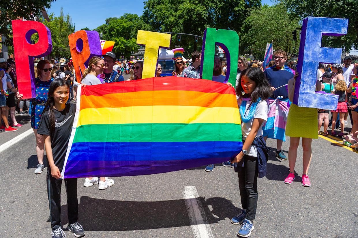 PORTLAND, OR - JUNE 16:  Two girls lead a segment of the parade with a rainbow flag followed by adults with the word