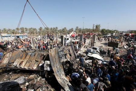 Residents gather at the site of a car bomb attack at a checkpoint in the city of Hilla