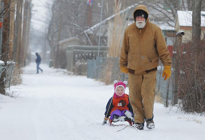 Ray Hughes pulls his grandson, Grant McMillen, 3, down an alley during a snow storm, Wednesday, Feb. 20, 2013 in Salina, Kan. Hundreds of snow plows and salt spreaders took to the highways of the nation's heartland Wednesday, preparing for a winter storm that could dump up to a foot of snow in some areas and bring dangerous freezing rain and sleet to others. (AP Photo/The Salina Journal, Tom Dorsey)