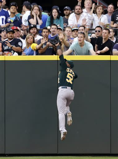 Oakland Athletics center fielder Yoenis Cespedes leaps at the wall for a fly ball from Seattle Mariners' Kyle Seager in the sixth inning of a baseball game Saturday, May 11, 2013, in Seattle. Cespedes made the catch. (AP Photo/Elaine Thompson)