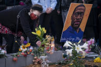 A demonstrator places flowers at a memorial outside Cup Foods as supporters gather to celebrate the murder conviction of former Minneapolis police officer Derek Chauvin in the killing of George Floyd, Tuesday, April 20, 2021, in Minneapolis. (AP Photo/John Minchillo)