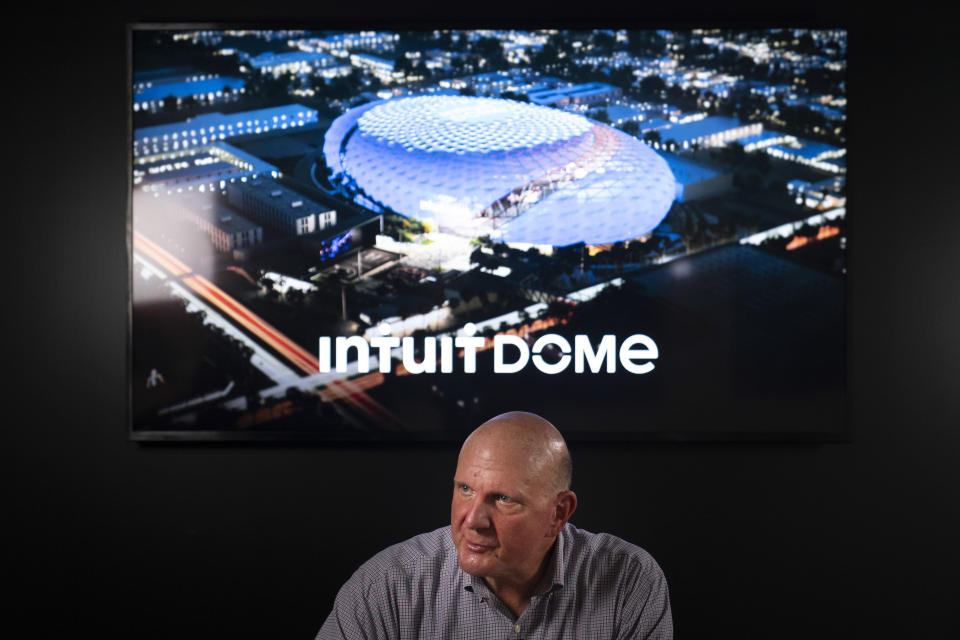 With a rendering of the proposed arena for the Los Angeles Clippers behind him, Clippers owner Steve Ballmer talks to a reporter during an interview with The Associated Press, Thursday, Sept. 16, 2021, in Los Angeles. (AP Photo/Jae C. Hong)