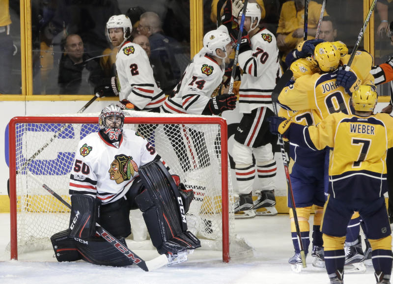 Chicago Blackhawks goalie Corey Crawford (50) looks up at the scoreboard as Nashville Predators players celebrate a goal by Filip Forsberg during the third period in Game 3 of a first-round NHL hockey playoff series Monday, April 17, 2017, in Nashville, Tenn. The Predators won 3-2 in overtime to take a 3-0 lead in the series. (AP Photo/Mark Humphrey)