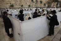 Ultra-Orthodox Jewish men pray ahead of the Jewish new year at the Western Wall, the holiest site where Jews can pray in Jerusalem's old city, Wednesday, Sept. 16, 2020. A raging coronavirus outbreak is casting a shadow over the normally festive Jewish New Year. With health officials recommending a nationwide lockdown, traditional family gatherings will be muted, synagogue prayers will be limited to small groups and roads will be empty. (AP Photo/Sebastian Scheiner)