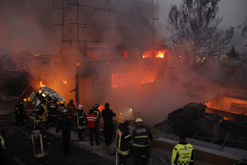 Firefighters work as a house burns after a gas tanker truck exploded on the highway in front of the house in the Mexico City suburb of Ecatepec, early Tuesday, May 7, 2013.  The blast killed and injured dozens, according to the Citizen Safety Department of Mexico State. Officials did not rule out the possibility the death toll could rise as emergency workers continued sifting through the charred remains of vehicles and homes built near the highway on the northern edge of the metropolis. (AP Photo/Gabriela Sanchez)