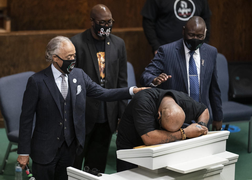 Terrence Floyd, brother of George Floyd, speaks during a prayer service at Greater Friendship Missionary Church, as The Rev. Al Sharpton, left, his brother Philonise Floyd and attorney Ben Crump, right, place their hands on his back, Sunday, March 28, 2021, in Minneapolis. Opening statements are set for Monday in the trial of a former Minneapolis police officer charged with murder and manslaughter in George Floyd's death. (Jerry Holt/Star Tribune via AP)