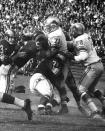FILE- In this undated file photo, unidentified members of the Los Angeles Rams NFL football team try and stop Detroit Lions defensive tackle Alex Karras (71) during a game in Michigan. For all the acclaim that followed, Karras died at age 77 in 2012 without one of the honors he coveted most: a bust in the Pro Football Hall of Fame. Better late than never, Karras will be formally enshrined as part of the Hall's Centennial Class of 2020. (Detroit Lions via AP)