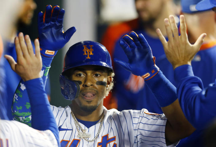 New York Mets' Francisco Lindor celebrates in the dugout after hitting a home run during the second inning of a baseball game against the New York Yankees Sunday, Sept.12, 2021, in New York. (AP Photo/Noah K. Murray)