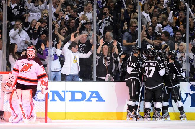LOS ANGELES, CA - JUNE 11:  Dwight King #74 , Alec Martinez #27 and Drew Doughty #8 of the Los Angeles Kings celebrate with teammate Trevor Lewis #22 after Lewis scored the third Kings' goal in first period against Martin Brodeur #30 of the New Jersey Devils in Game Six of the 2012 Stanley Cup Final at Staples Center on June 11, 2012 in Los Angeles, California.  (Photo by Harry How/Getty Images)