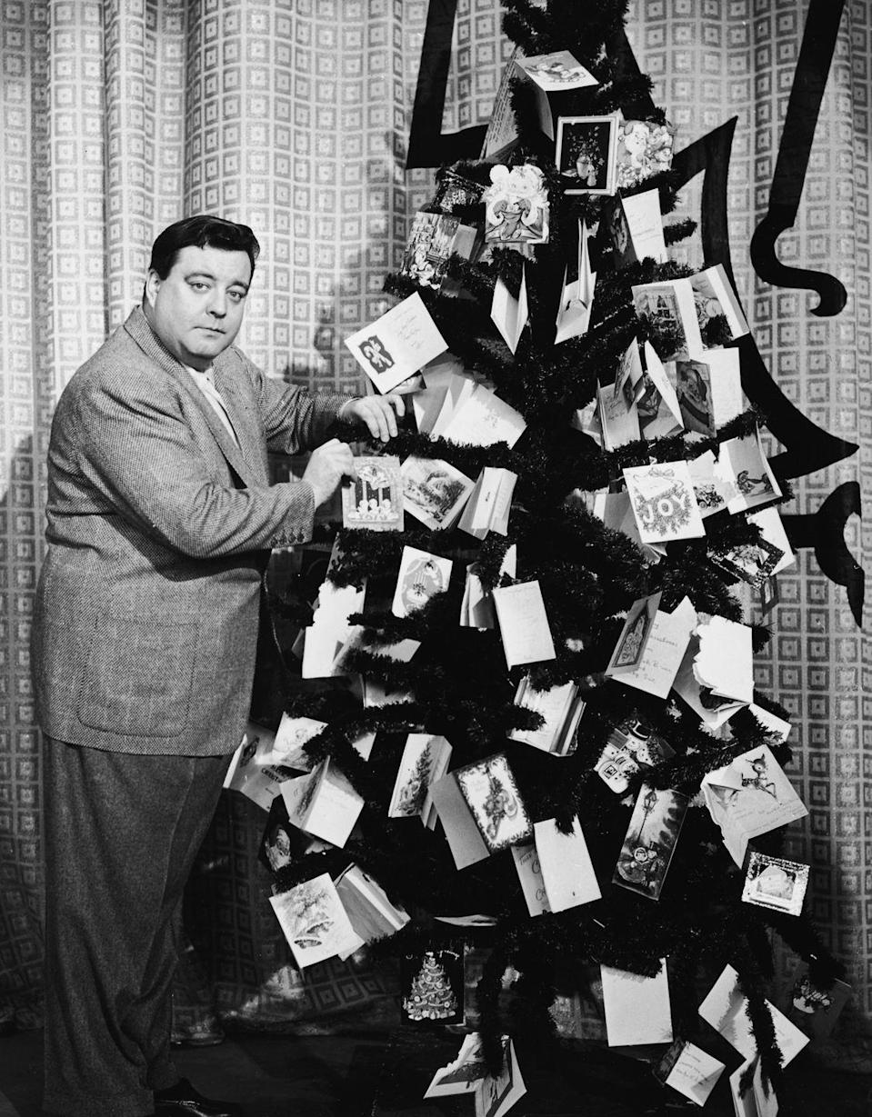 <p>Wearing a grey tweed suit, comedian Jackie Gleason decorated a Christmas tree with holiday greeting cards in 1954. Why? We're not 100% sure.</p>
