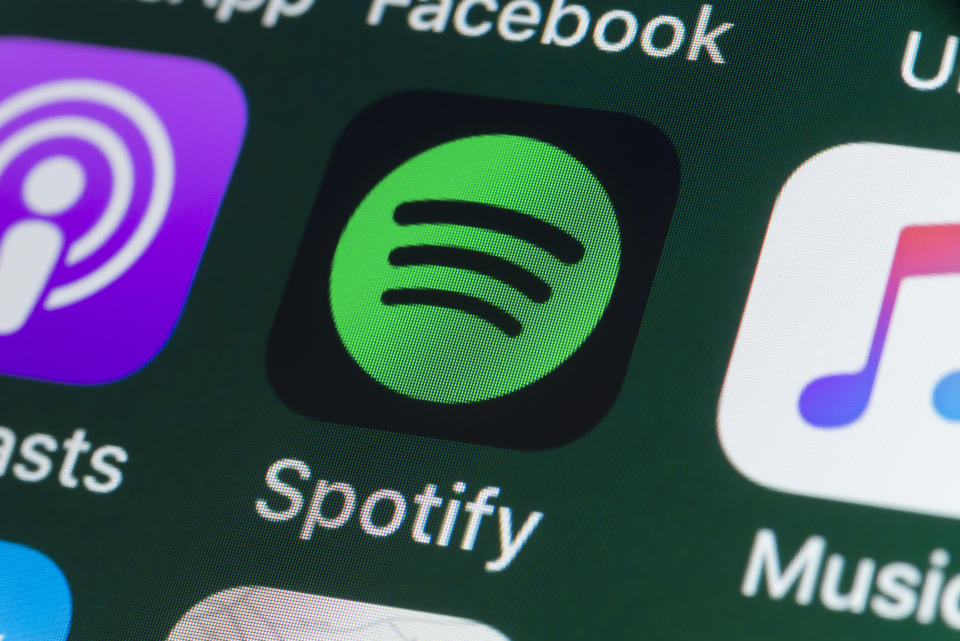 London, UK - July 31, 2018: The buttons of the music streaming app Spotify, surrounded by Podcasts, Apple Music, Facebook and other apps on the screen of an iPhone.