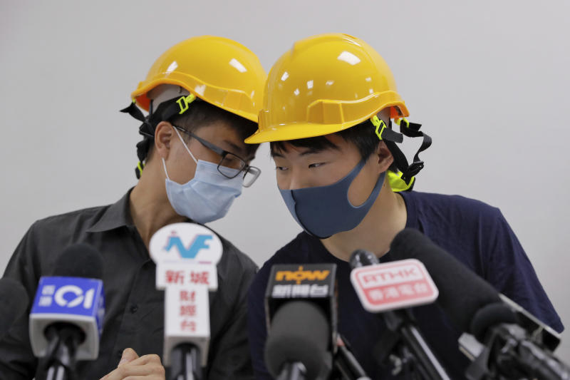 "Protesters Jerry Chan, right, chats with Linus Kim during a press conference in Hong Kong, Tuesday, Aug. 6, 2019. Hong Kong protesters Tuesday condemned what they call the government's ""empty rhetoric"" and instances of alleged police abuse in an inaugural ""People's Press Conference."" (AP Photo/Kin Cheung)"