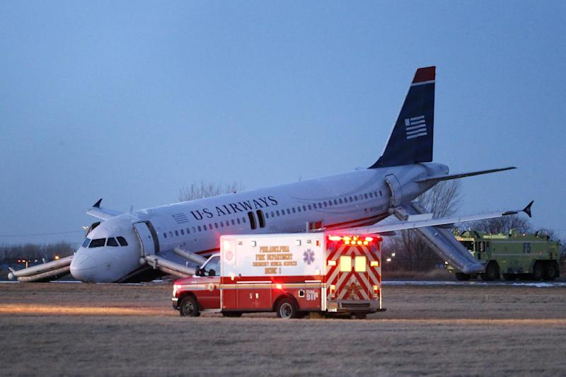Emergency vehicles drive past a damaged US Airways jet at the end of a runway at the Philadelphia International Airport, Thursday, March 13, 2014, in Philadelphia. Airline officials said the flight was heading to Fort Lauderdale, Fla., when the pilot was forced to abort takeoff around 6:30 p.m., after the front landing gear failed. An airport spokeswoman said no injuries have been reported. (AP Photo/Matt Slocum)