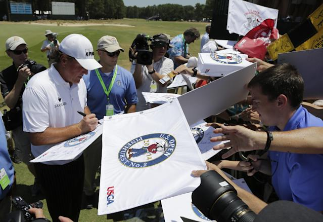 Fans try for a autograph from Phil Mickelson after a practice round for the U.S. Open golf tournament in Pinehurst, N.C., Tuesday, June 10, 2014. The tournament starts Thursday. (AP Photo/Chuck Burton)