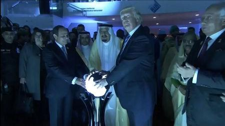 U.S. President Donald Trump places his hands on a glowing orb as he tours with other leaders the Global Center for Combatting Extremist Ideology in Riyadh, Saudi Arabia May 21, 2017.  Saudi TV via  Reuters