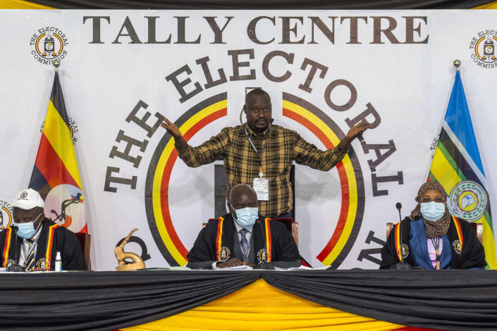 Uganda Electoral Commission chairman Simon Byabakama, seated center, declares Ugandan President Yoweri Kaguta Museveni winner of the presidential elections in Kampala, Uganda, Saturday Jan. 16, 2021. Uganda's electoral commission says longtime President Yoweri Museveni has won a sixth term, while top opposition challenger Bobi Wine alleges rigging and officials struggle to explain how polling results were compiled amid an internet blackout. In a generational clash widely watched across the African continent, the young singer-turned-lawmaker Wine posed arguably the greatest challenge yet to Museveni. (AP Photo/Jerome Delay)