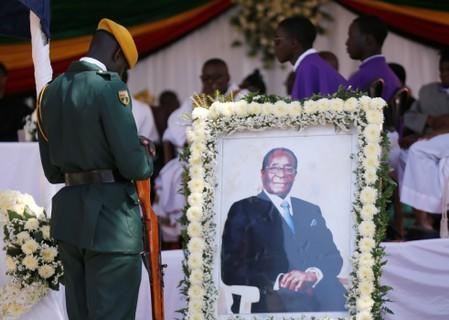 Soldier stands beside a picture of former Zimbabwean President Robert Mugabe during a church service at his rural village in Kutama, Zimbabwe
