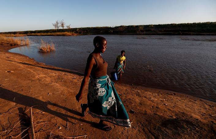 "Maria Jofresse, 25, walks at the edge of the Muda River to meet her father Joao Jofresse, who works on a water taxi, in the village of Cheia which means ""Flood"" in Portuguese, near Beira, Mozambique, April 2, 2019. (Photo: Zohra Bensemra/Reuters)"