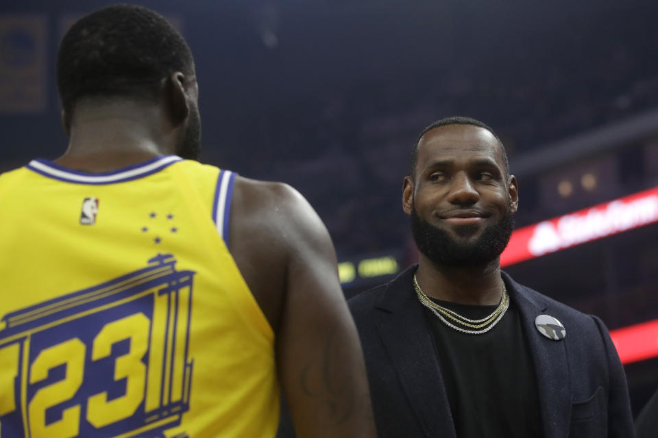 Injured Los Angeles Lakers forward LeBron James, right, smiles while talking with Golden State Warriors forward Draymond Green during the first half of an NBA basketball game in San Francisco, Thursday, Feb. 27, 2020. (AP Photo/Jeff Chiu)