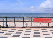 """Entrance to a beach is barricaded with sign read in Vietnamese """"Fight COVID-19 together, no beach activities"""" in Vung Tau, Vietnam, Monday, Sept. 20, 2021. In Vung Tau, just outside Ho Chi Minh city, streets are sealed and checkpoints are set up to control the movement of people. Barbed wire, door panels, steel sheets, chairs and tables are among materials being used to fence up alleys and isolate neighborhoods.(AP Photo/Hau Dinh)"""