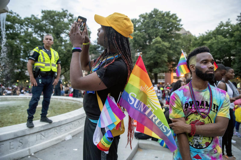 People watch the conclusion of the Capitol Pride Parade at Dupont Circle in Washington, Saturday, June 8, 2019. (AP Photo/Andrew Harnik)