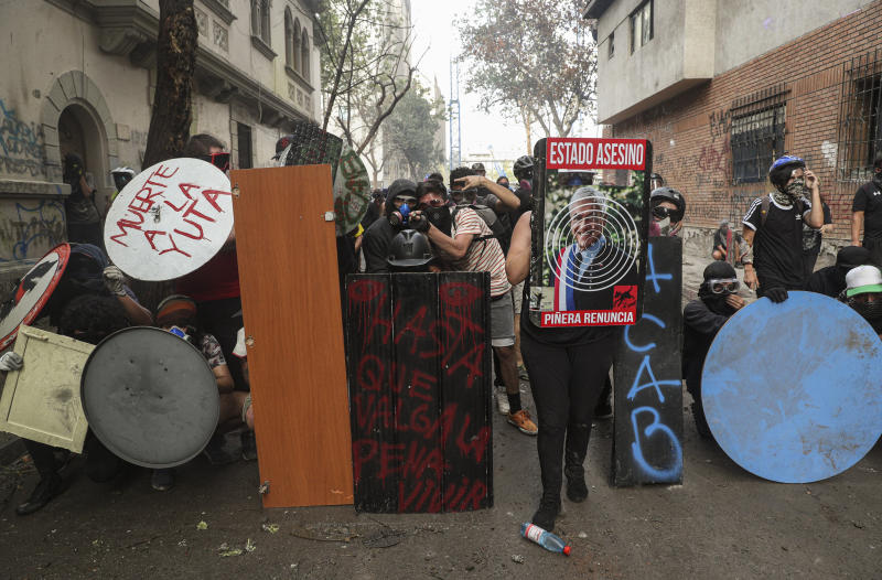 Anti-government demonstrators take cover behind a shield wall as they clash with police in Santiago, Chile, Monday, Nov. 18, 2019. According to the Medical College of Chile at least 230 people have lost sight after being shot in an eye in the last month while participating in the demonstrations over inequality and better social services. (AP Photo/Esteban Felix)