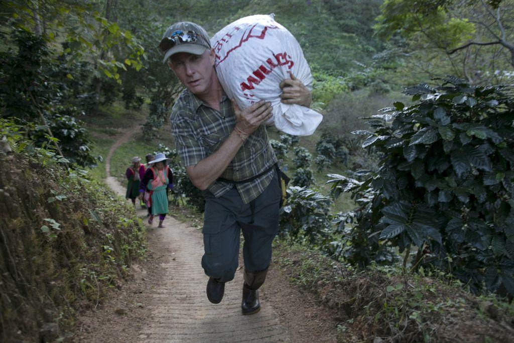 ay Buerger, owner of Thai High Ventures, carries a large bag of freshly picked coffee beans at the Thai High coffee farm in Phrao, northern Thailand. The organic fair trade coffee farm was chosen to help produce the Black Ivory Coffee. The new brand of coffee is produced by harvesting the beans from the dung of a Thai elephant.