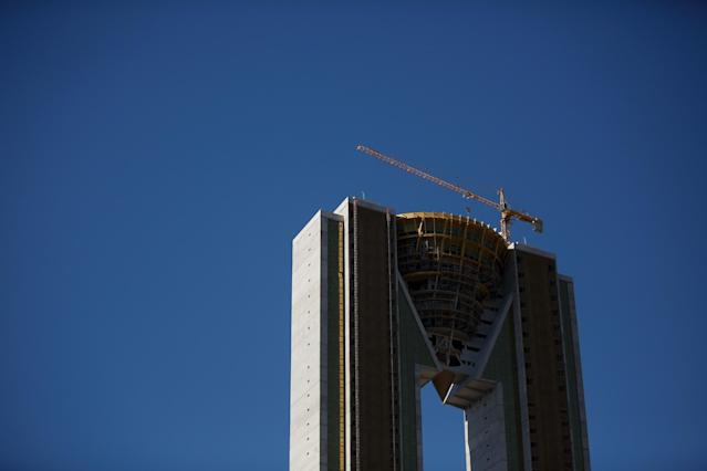 """BENIDORM, SPAIN - AUGUST 09: A crane stands on top of the unfinished InTempo building on August 9, 2013 in Benidorm, Spain. The construction of the In Tempo building began during the economic boom and was meant open in 2009 as the tallest residential building within the E.U. at almost 200 metres high. However after a catalogue of building problems the 47-story twin tower building remains unfinished and has been transferred to the SAREB or """"Bad Bank"""". (Photo by Pablo Blazquez Dominguez/Getty Images)"""