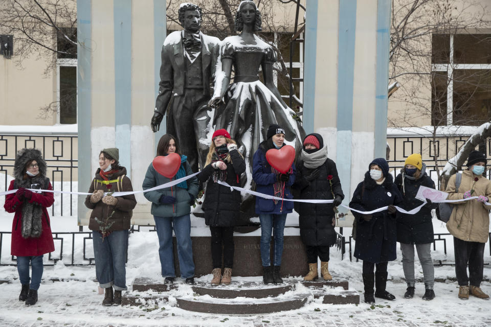 Women hold a white ribbon as they stay in a line during a rally in support of jailed opposition leader Alexei Navalny, and his wife Yulia Navalnaya in Moscow, Russia, Sunday, Feb. 14, 2021. The weekend protests in scores of cities last month over Navalny's detention represented the largest outpouring of popular discontent in years and appeared to have rattled the Kremlin. (AP Photo/Pavel Golovkin)