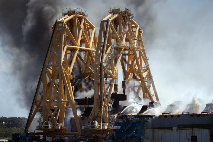Firefighters working from the towering crane being used to dismantle the ship, hose down a fire in the overturned cargo ship Golden Ray, Friday, May 14, 2021, Brunswick, Ga. The Golden Ray had roughly 4,200 vehicles in its cargo decks when it capsized off St. Simons Island on Sept. 8, 2019. Coast Guard Petty Officer 2nd Class Michael Himes says there have been no injuries and all demolition crew members were safely evacuated. (AP Photo/Stephen B. Morton)