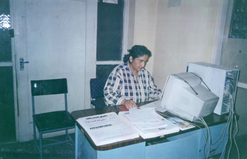 Marzia Babakarkhail works at her desk in Afghanistan in the 1990s.