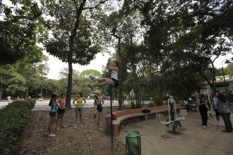 In this photo taken July 1, 2012, Keryne Este practices pole dancing at an outdoor gym as her friends watch during one of their weekend outings to a public park in Caracas, Venezuela. Pole dancing may have started out in strip clubs, but since the 1990s, it's become an all-ages exercise and sport phenomenon the world over. Now, it's hit the streets in Venezuela, a country that's made beauty and fitness a cult and minted more Miss Universes than any other except the United States. (AP Photo/Fernando Llano)