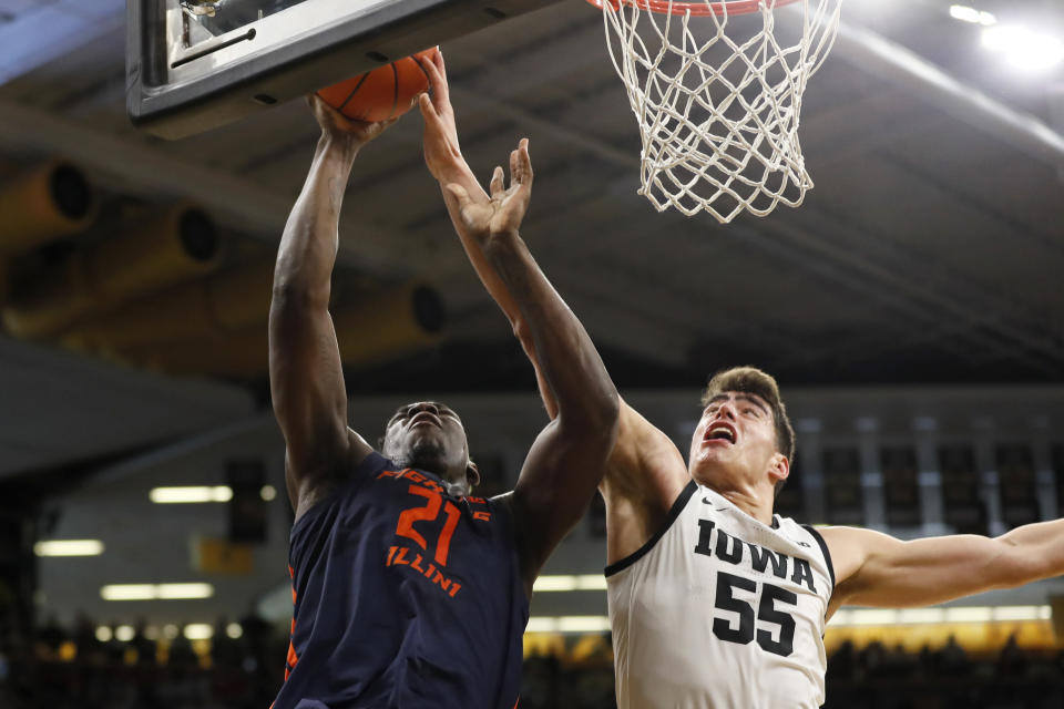 FILE - Illinois center Kofi Cockburn (21) drives to the basket past Iowa center Luka Garza (55) during the first half of an NCAA college basketball game in Iowa City, Iowa, in this Sunday, Feb. 2, 2020, file photo. For all the success Luka Garza has experienced at Iowa, he can't forget one moment of failure. With 1.6 seconds left against Illinois last March, Garza had a chance to tie the game when he took an inbound pass near the basket. Kofi Cockburn blocked his shot, and the Illini won 78-76. (AP Photo/Charlie Neibergall, File)