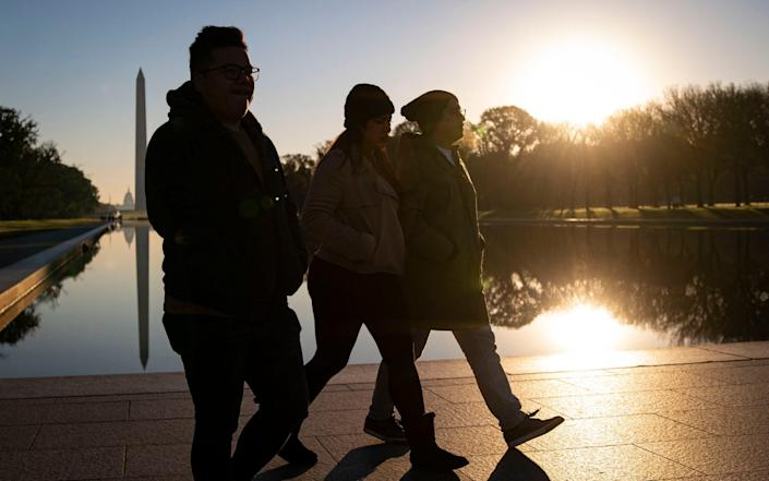 People walk past the Reflecting Pool along the National Mall near the Lincoln Memorial - Getty Images North America