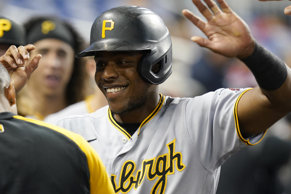 Pittsburgh Pirates Ke'Bryan Hayes (13) is greeted by the team after scoring during the first inning of the team's baseball game against the Miami Marlins, Saturday, Sept. 18, 2021, in Miami. (AP Photo/Marta Lavandier)