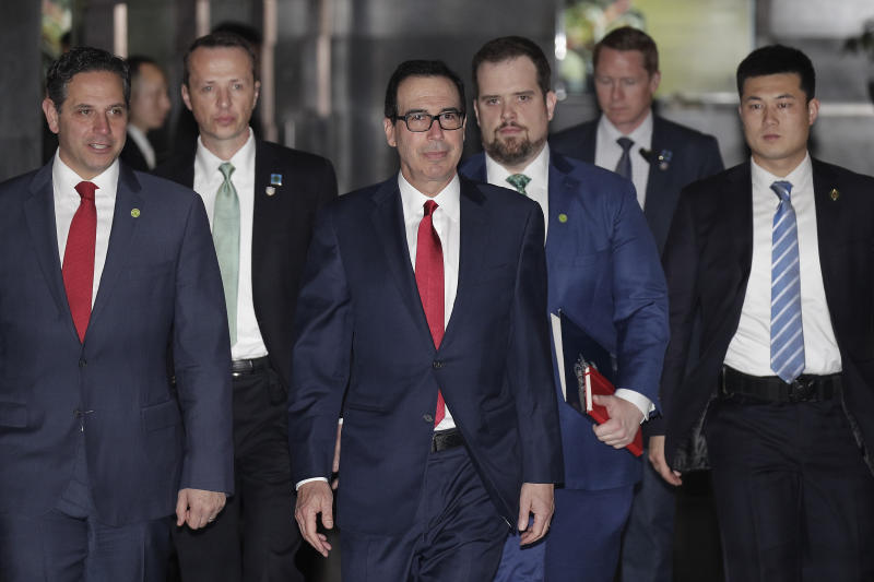 U.S. Treasury Secretary Steven Mnuchin, center, escorted by bodyguards and a delegation leaves a hotel in Beijing, Friday, March 29, 2019. U.S. trade negotiators lead by Mnuchin and Trade Representative Robert Lighthizer arrived in Beijing to start a new round of talks aimed at ending a tariff war over China's technology ambitions as officials hint they might be making progress. (AP Photo/Andy Wong)