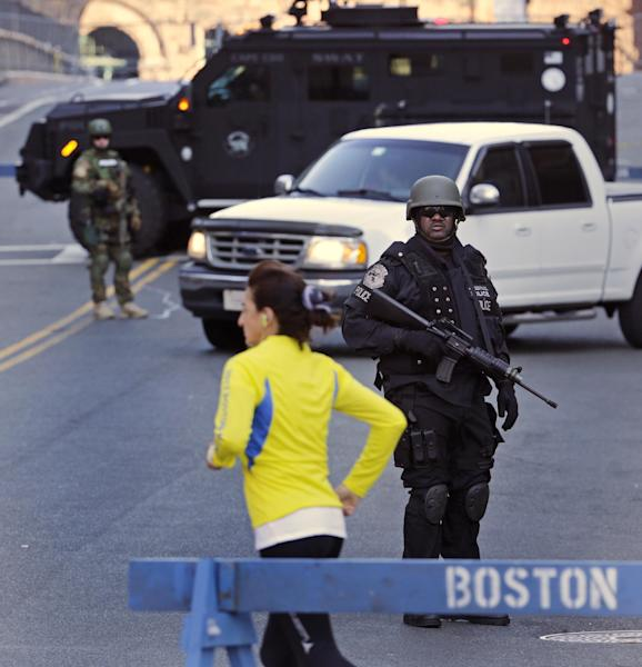 A runner passes a police officer dressed in tactical gear, who blocks a road leading to the Boston Marathon route, the morning after explosions killed three and injured more than 140 in Boston, Tuesday, April 16, 2013. The bombs that blew up seconds apart at the finish line of one of the world's most storied races left the streets spattered with blood and glass, and gaping questions of who chose to attack at the Boston Marathon and why. (AP Photo/Charles Krupa)