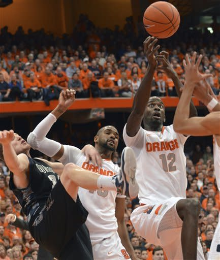 Syracuse's Baye Moussa Keita, right, tries to grab a loose ball as Georgetown's Nate Lubick and James Southerland get tangled up during the first half in an NCAA college basketball game in Syracuse, N.Y., Saturday, Feb. 23, 2013. (AP Photo/Kevin Rivoli)