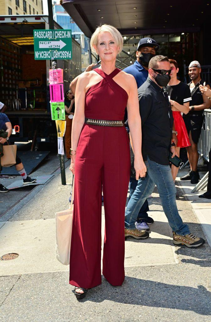 """<p>Mirroring her character's boss woman energy, Miranda Hobbes's Cynthia Nixon wore <a href=""""https://www.instagram.com/p/CRXW2ULjEXR/"""" rel=""""nofollow noopener"""" target=""""_blank"""" data-ylk=""""slk:a red dash halter jumpsuit by Likely"""" class=""""link rapid-noclick-resp"""">a red dash halter jumpsuit by Likely</a> paired with YSL studded leather platform sandals Soko """"Capped Quill"""" dangle earrings. </p>"""